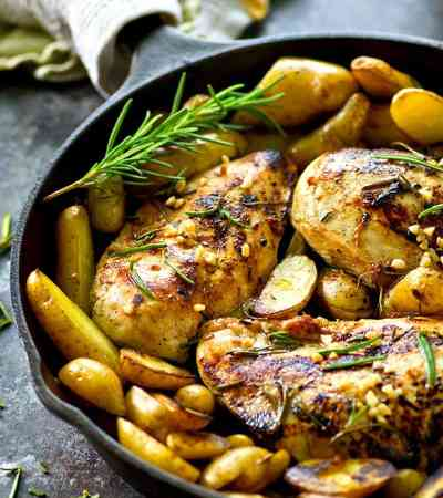 A fragrant rosemary garlic olive oil marinade gives this rosemary garlic chicken INCREDIBLE flavor and it's all roasted up with soft fingerling potatoes in one pot!