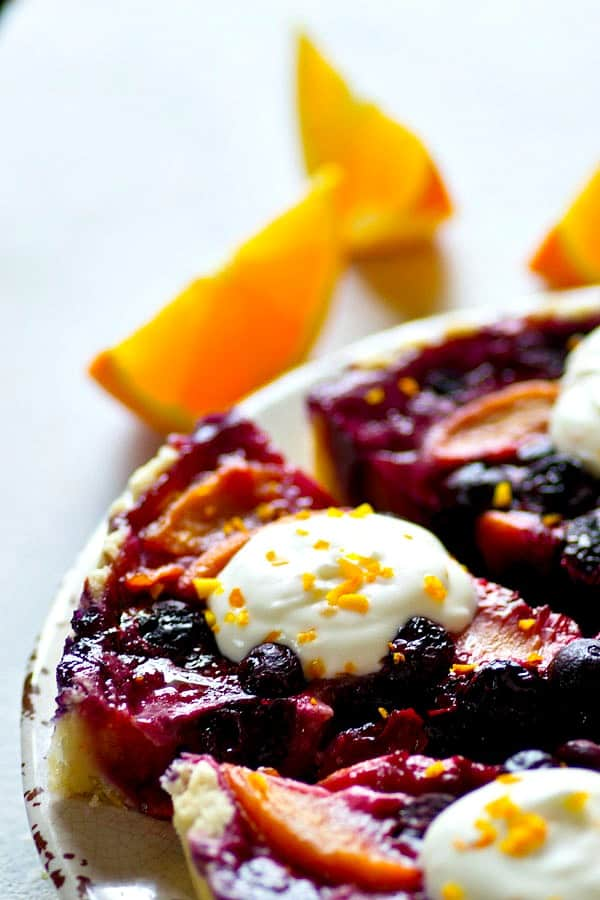 Juicy blueberries and peaches are a match made in heaven in this pretty blueberry peach tart that's covered with a tangy, irresistible citrus whipped cream!
