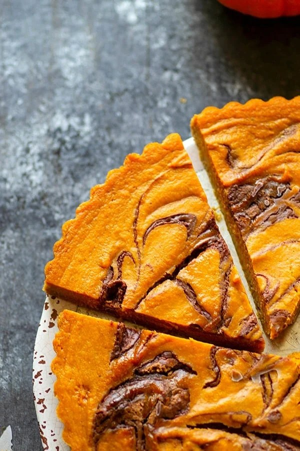 Milk Chocolate Swirl Pumpkin Tart - Silky pumpkin pie filling is swirled with a luscious ribbon of milk chocolate to make one swoon-worthy holiday tart!