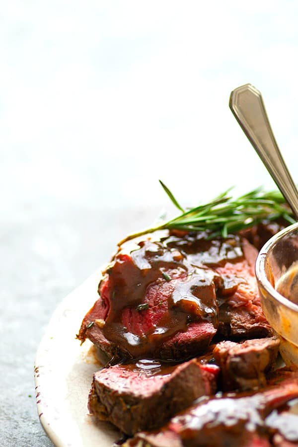 Rosemary Garlic Butter Beef Tenderloin - Roasted to perfection in a flavorful rosemary garlic butter and covered in hearty red wine sauce, this rosemary garlic butter beef tenderloin is an easy, yet impressive entree for any dinner crowd.