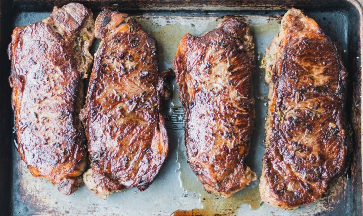 4 brown and crispy New York Strip steaks on a sheet tray.