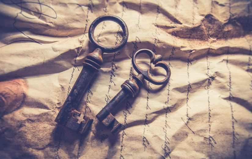 two black skeleton keys on an old paper