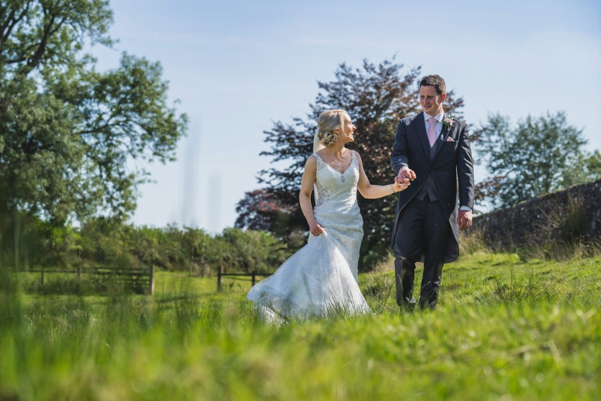 Wedding couple walking through field in Carmarthenshire