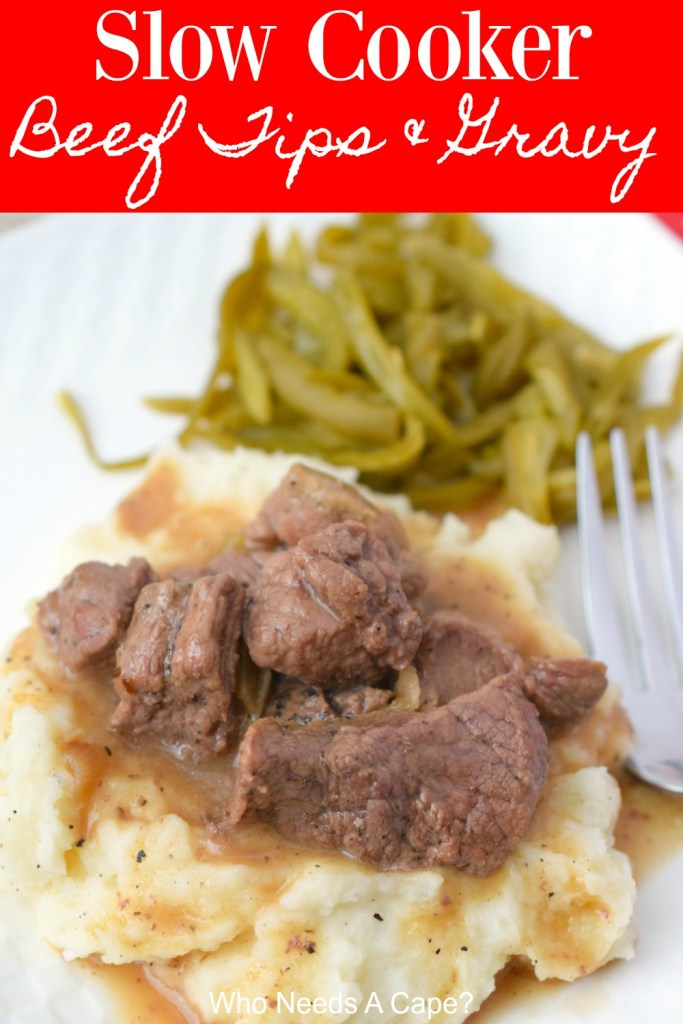 beef tip pieces and gravy on mashed potatoes with green beans and fork on white plate