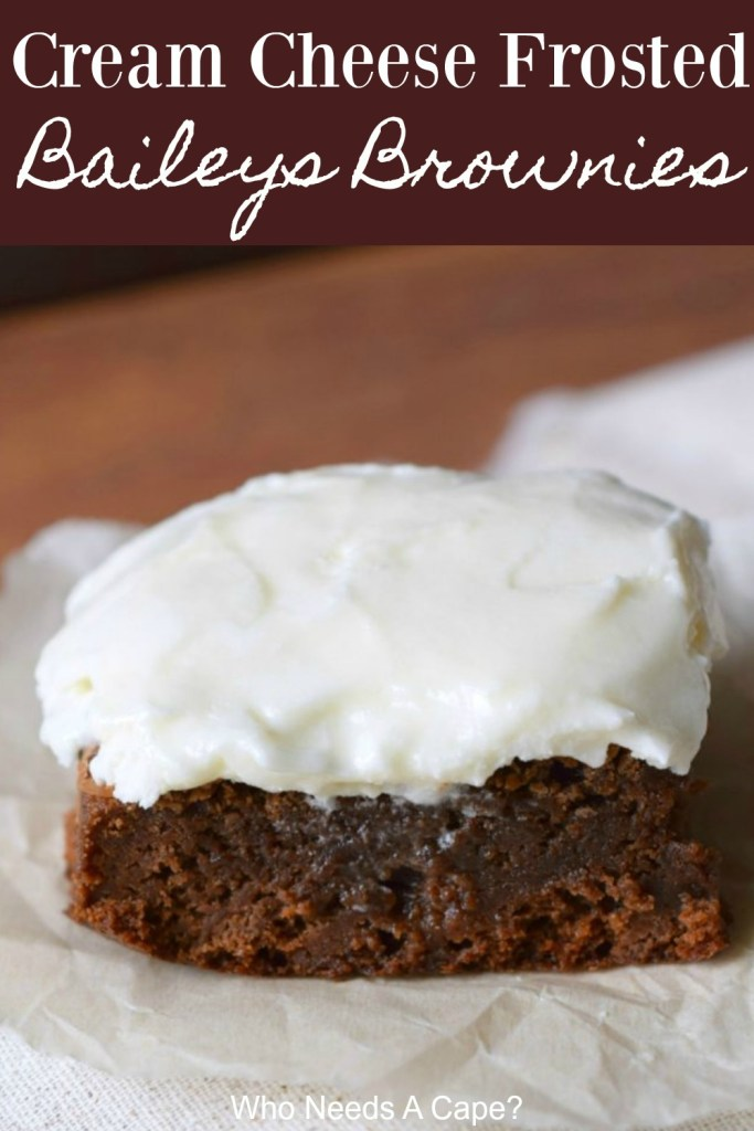 cut brownie serving on white parchment paper topped with cream cheese baileys frosting