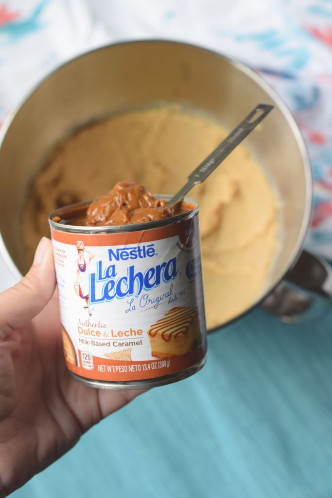 hand holding can of dulce de leche over top of mixing bowl next to floral fabric