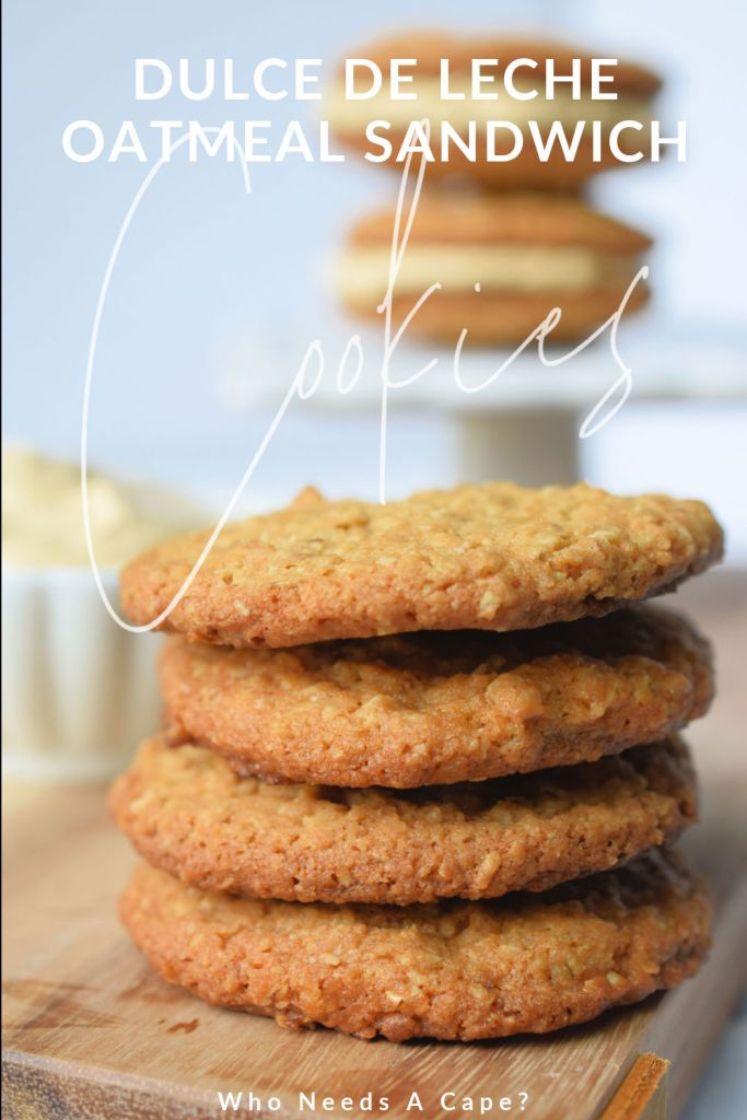stack of cookies in front of finished sandwich cookies sitting on white stand next to white bowl containing frosting