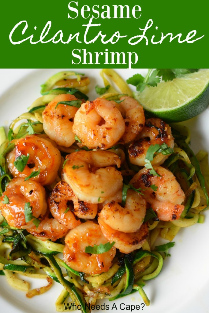 shrimp on bed of zucchini noodles on white plate with lime