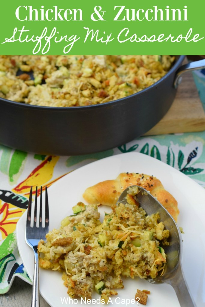 chicken & zucchini stuffing mix casserole on white plate with fork and crescent roll sitting on floral cloth and next to pan