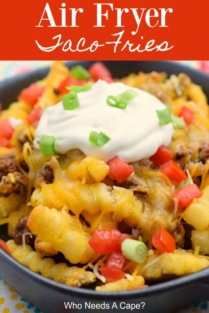 black dish containing air fryer taco fries with french fries, ground beef, diced tomato, sour cream and sliced green onions