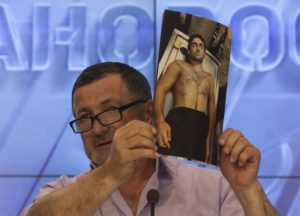 Ibragim Todashev's father, displaying an autopsy photo of his son.