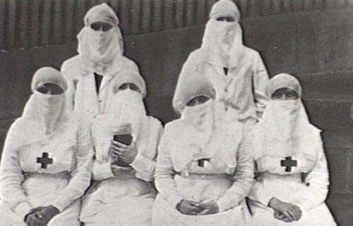 Group of women swathed in white garb as protection from deadly flu virus.