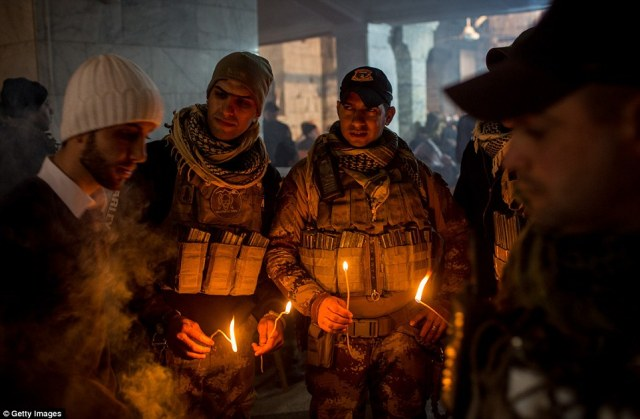Soldiers from the Iraqi Army Special Forces light candles during the Christmas mass at the Mar Shimoni Church in Bartella