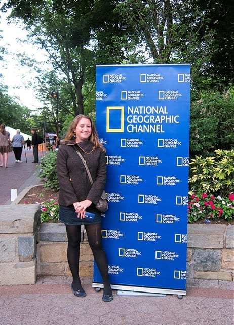Me in Front of a National Geographic Sign - Should You Start a Travel Blog: The Dirty Truth