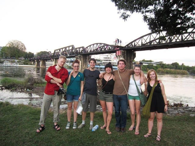A Group Tour in Front of a Bridge - How to Meet People While Traveling as a Couple