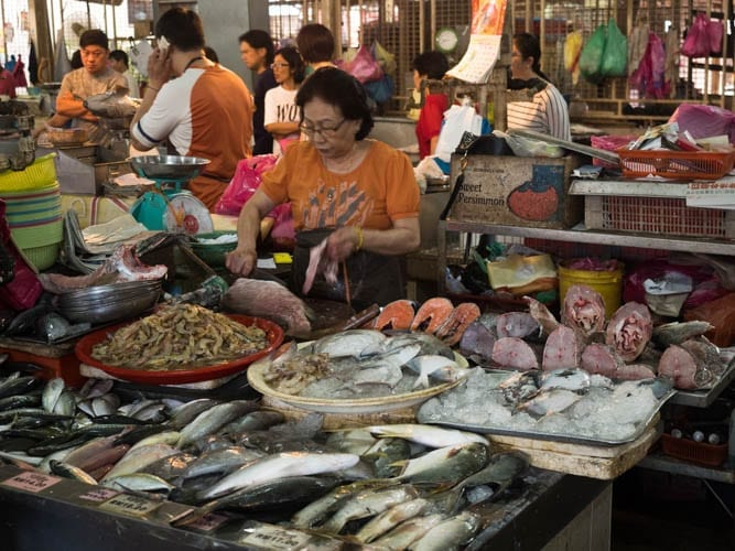 A Woman Gutting a Fish in the Market in Penang - A Luxury Malaysia Holiday