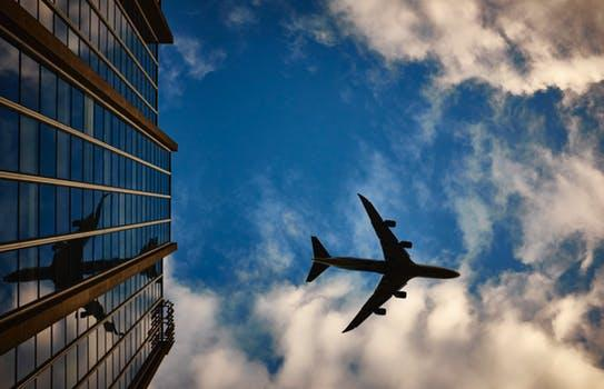 Plane Flying Over a Glass Building - 8 Business Travel Hacks to Make it More Comfortable