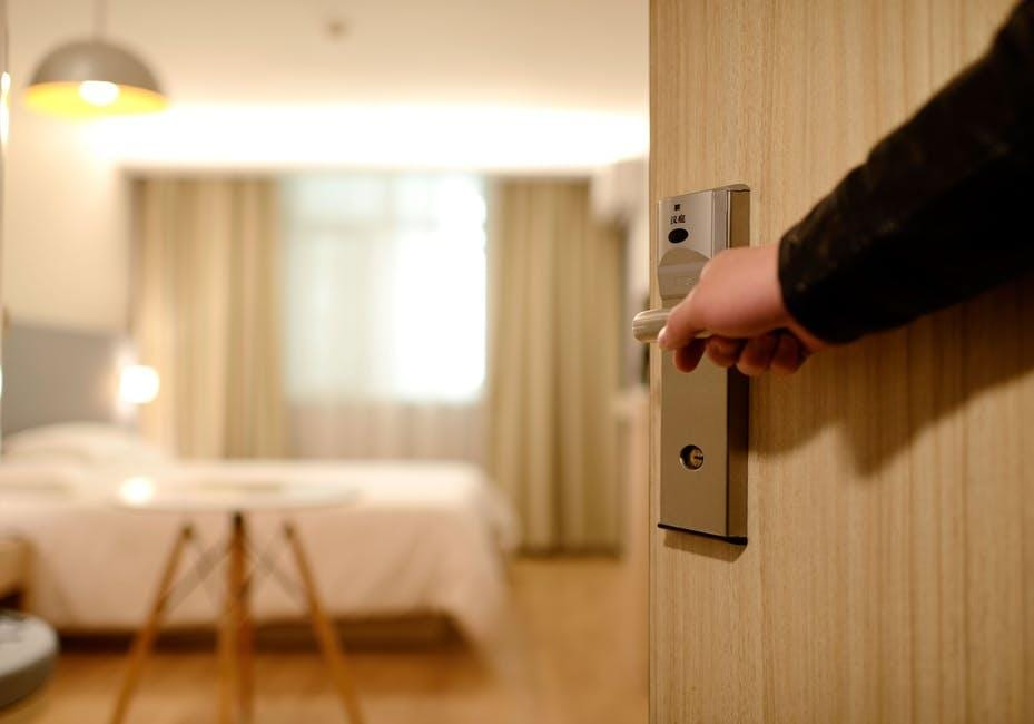 A Person Opening Up a Door into a Hotel Room - 8 Business Travel Hacks