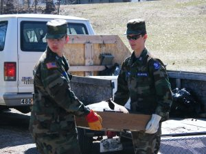 Photo by Maj. Todd Mandel - Cadet Master Sergeant Colton Wilbur and Cadet Staff Sergeant T.J. Henson take a television to the dumpster.