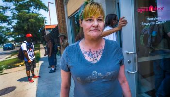 Charity Johnston waits outside of United Methodist Open Door, 402 E. 2nd St., on Tuesday afternoon. It serves as a resource center for those without permanent homes by providing hot showers, a laundry service and a place to rest or eat. (Fernando Salazar/The Wichita Beacon)