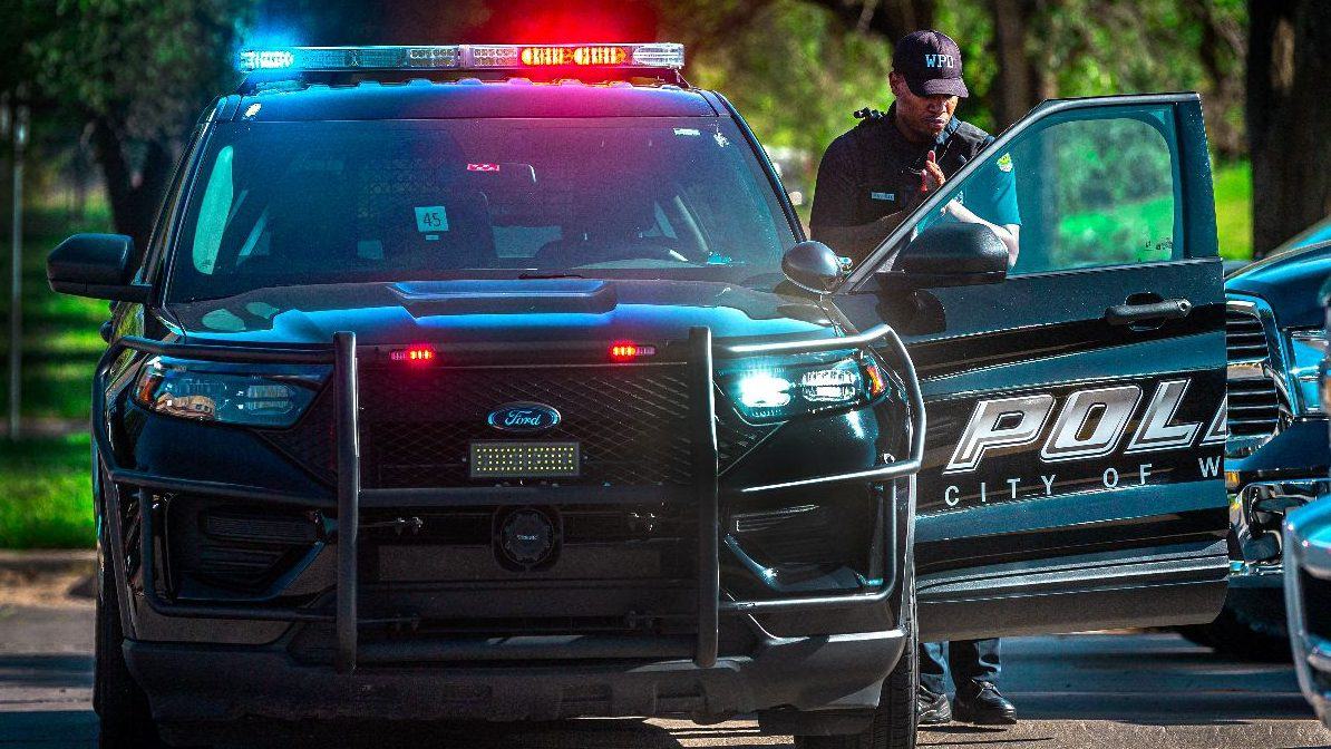 A Wichita police officer stands next to his cruiser during shift change at the North Police substation. Wichita police maintain a confidential database of about 3,000 Wichita residents deemed suspicious as gang members or associates. (Fernando Salazar/The Beacon)