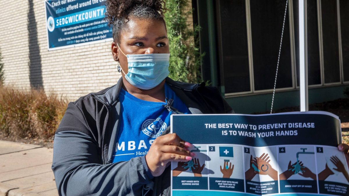 Stacey Roundtree, a Sedgwick County COVID Ambassador, holds educational materials from backpacks given to participants at the COVID-19 Vaccine Incentive Clinic at the Sedgwick County Health Department on Oct. 16. (Fernando Salazar/The Beacon)