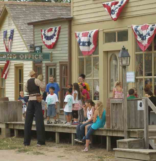 County Fair at Cowtown - man on stilts entertaining a crowd with children
