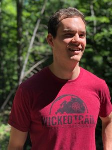 An ultrarunner smiles wearing his Wicked Trail shirt.