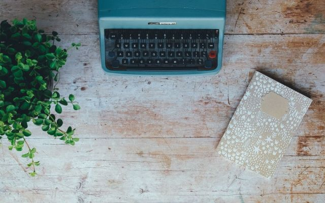 An image of a typewriter, a notebook and a plant to go with the page inviting people to share their writing.
