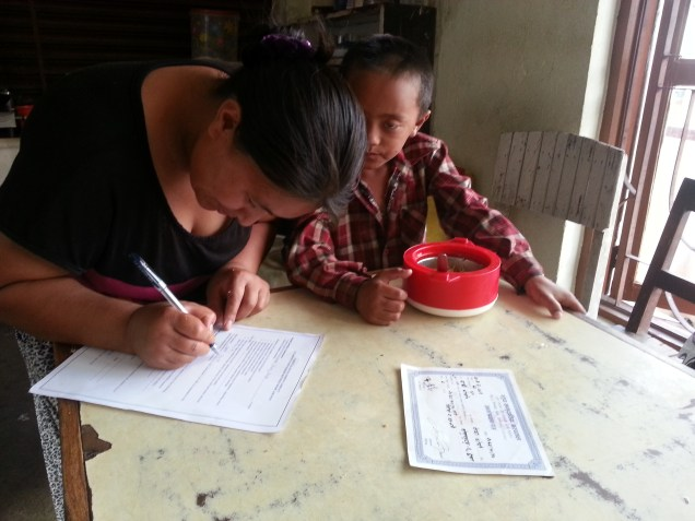 Sarki's wife signing the parental contract form in front of her son Pasang.