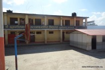 View of the courthard. The yellow building is condemned due to earthquake damage. Temporary classrooms have been built just in front...