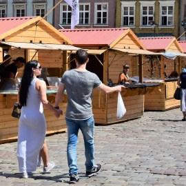 Jarmark Świętojański w Poznaniu. Dwoje ludzi spaceruje po płycie rynku.
