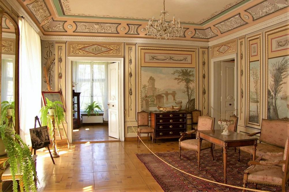 Wnętrza pałacu w Lewkowie. Zabytkowe meble, dywany oraz obrazy na ścianach.