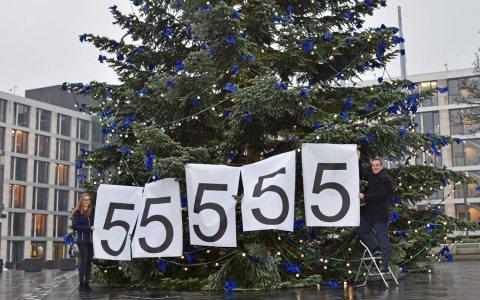 Lea Wagner und Dr. Ralph Glodek vom R+V-Nachhaltigkeitsteam befestigen das Ergebnis der Weihnachtsspendenaktion am Tannenbaum vor der Wiesbadener R+V-Zentrale. ©2017 R+V