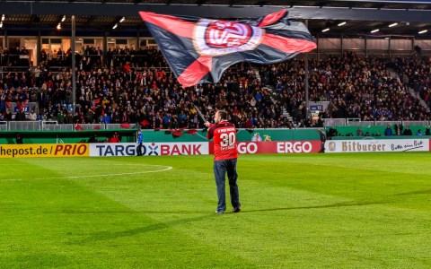 SV Wehen Wiesbaden, Heimspiel. Auf dem Rasen wird die Fahne geschwenkt. ©2018 Volker Watschounek