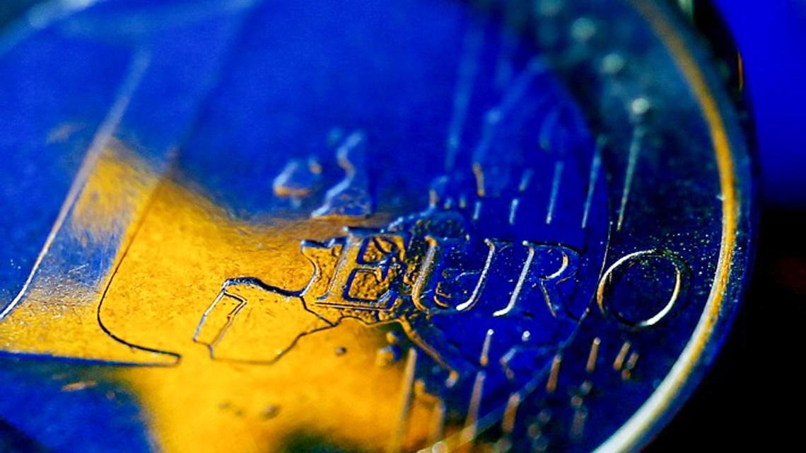 Die Fahne der Europäischen Union (EU) spiegelt sich in einer Euro-Münze. Foto:dpa