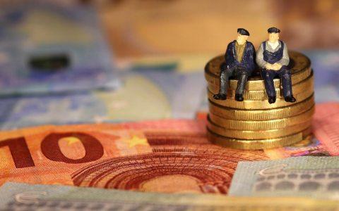 Zwei Renter sitzen auf einem Berg 50 Cent Münzen, umgeben von Euro Scheinen