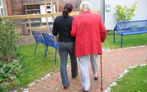 Alte Frau geht am Arm einer jungen Frau spazieren.