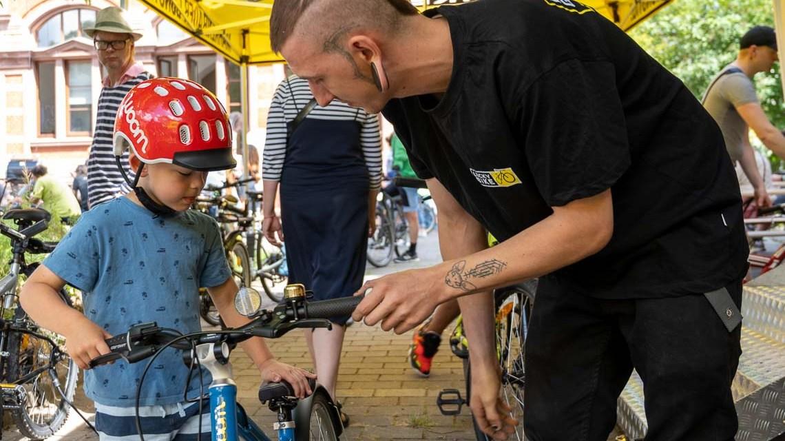 Fahrradfest: Fahrradreparatur und Fahrradcheck mit Lucky Bike: Kai Ehmann hat die Bremse von Konstantins Fahrrad nachgestellt. Foto: Volker Watschounek
