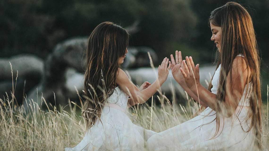 Zwei Mädchen sitzen auf einer Wiese und spielen.