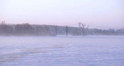 Stürmisch weht der Wind den losen Schnee über die Eisfläche , zugefrorener Stausee