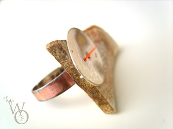 side view of ring with clock parts and aged ceramics