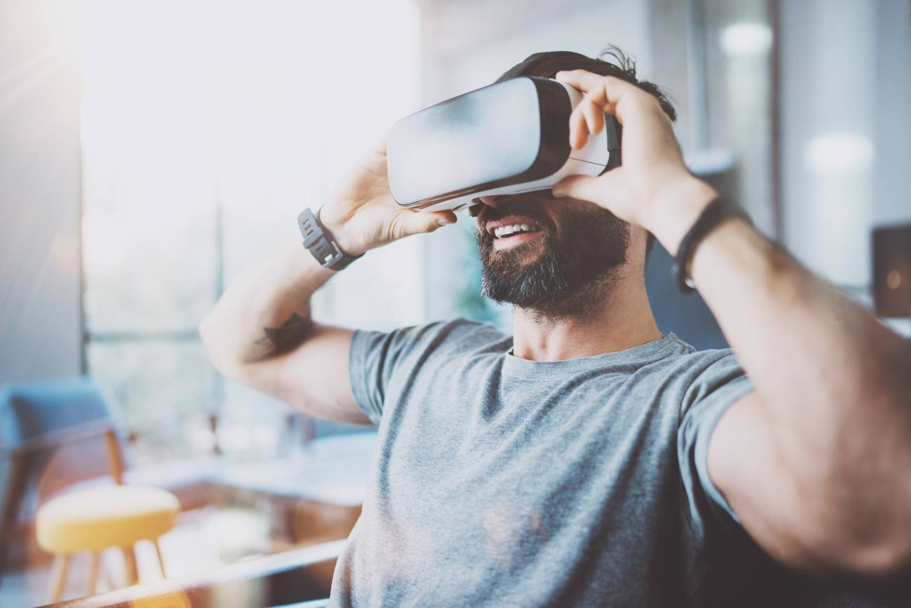 Bearded young man wearing virtual reality goggles in modern coworking studio. Smartphone using with VR headset in office. Horizontal, blurred.