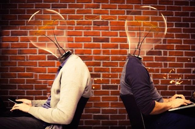 Zwei Menschen sitzen Rücken an Rücken mit Glühbirnen statt Köpfen