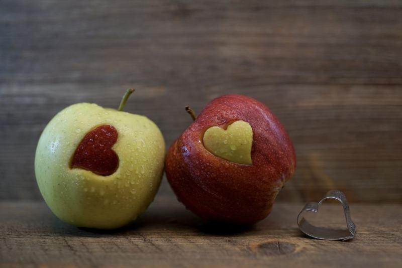 Zwei Äpfel mit ausgestochenen Herzen
