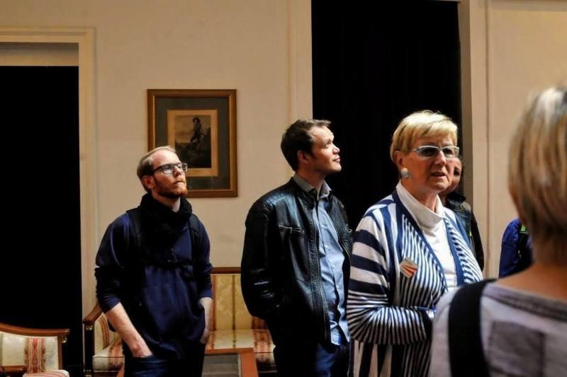 Drei Personen in einem Raum, im Hintergrund ein Bild von Erzherzog Johann.