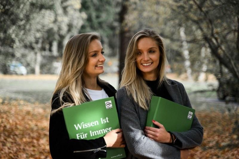 Zwei junge Teilnehmerinnen vom Vorbereitungskurs zur Berufsmatura mit dem WIFI Kursbuch am Arm.