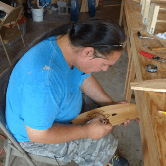 Wayne decorating one of the canoe's two inini-bagoog with a turtle symbol (Photo Credit: Colin Connors)