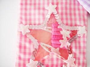 Detská luxusná kockovaná taštička pre malé princezné sa vždy hodí. Obsahuje gumičky s ozdobou a sponky. Je praktická a vyrobená z výborného materiálu.Farba- ružová. Rozmer: 10cm x 21cm.