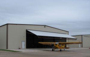 Aircraft hangar and Piper Cub airplane, photo credit wikiWings